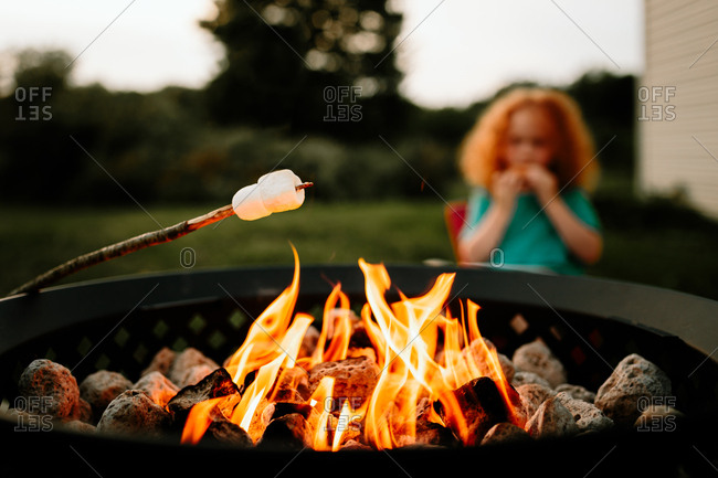 marshmallow roasting over fire pit in front of little boy eating s