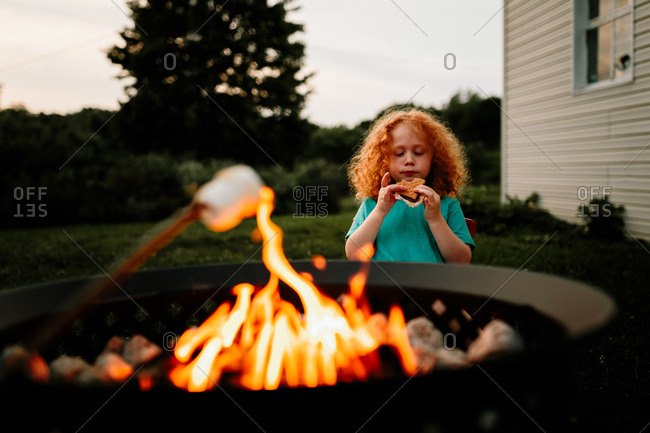 Boy eating a fresh s'more by backyard fire