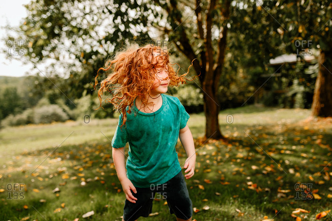 Young boy shaking wet hair in backyard