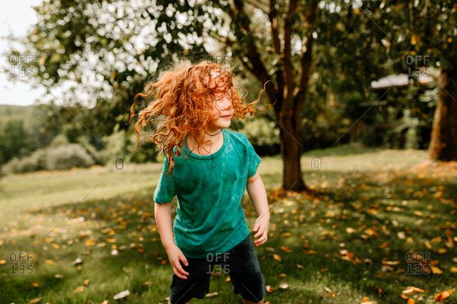 Young boy shaking wet hair in backyard