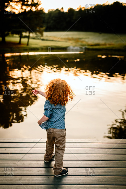 Little boy throwing rocks into pond at sunset