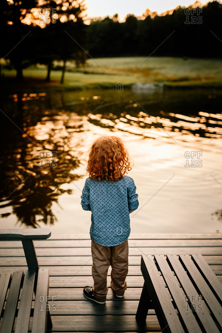 Boy watching sunset on pond dock