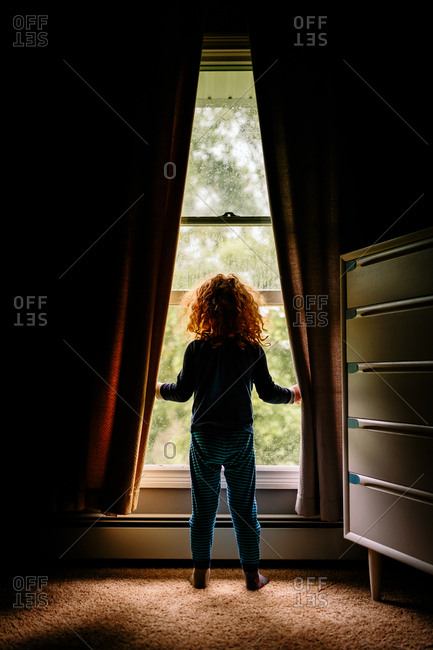 Child looking out rainy window