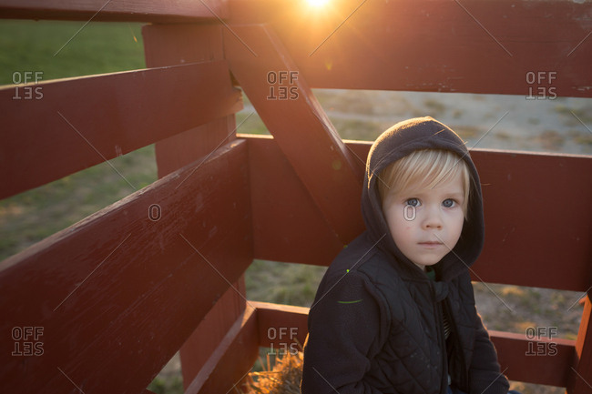 Little blonde boy with hoodie sitting in fenced ion corner at sunset