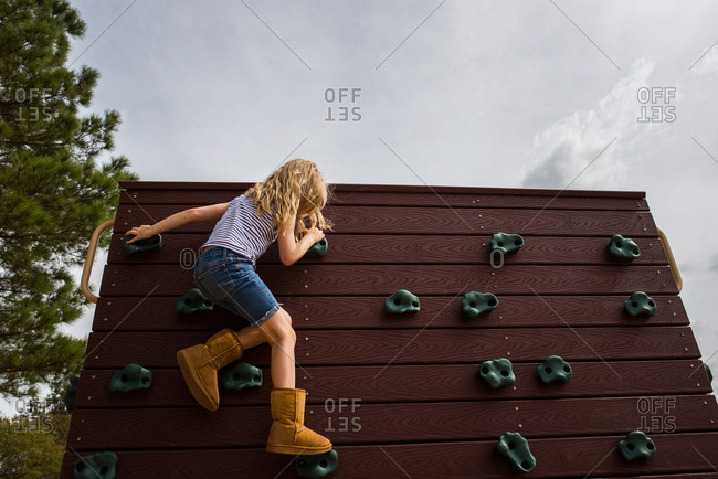 Adolescent girl at top of climbing wall