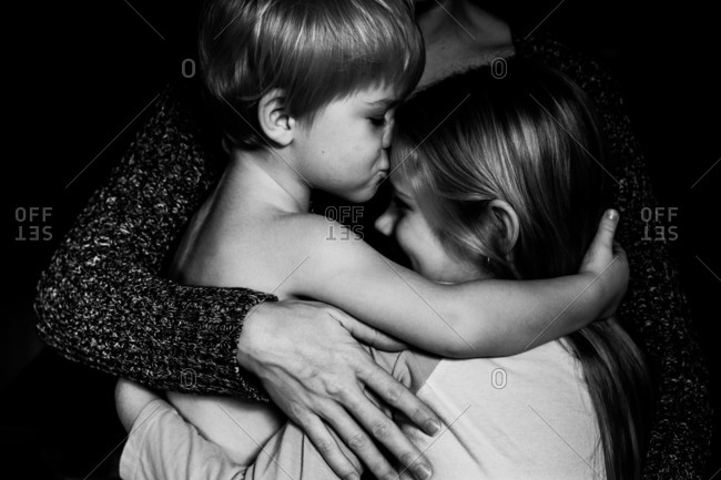 Mother's arm around little brother kissing big sister on forehead