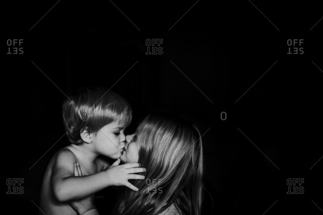 Loving siblings giving each other a kiss