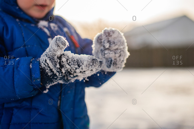 Small child looking at mittens covered ion snow