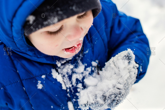 Little boy eating snow outside from palm of hand