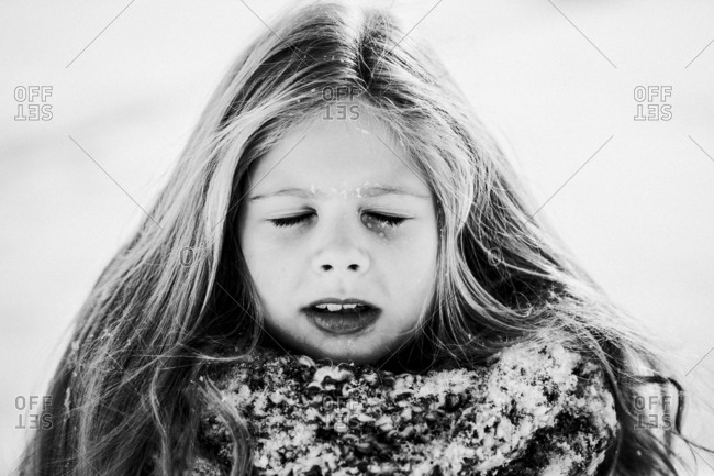 Young girl with snowflakes melting on closed eyelids