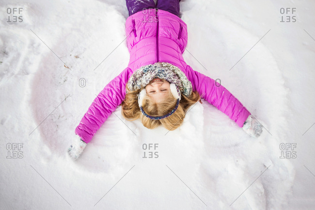 Happy little girl making snow angel on ground