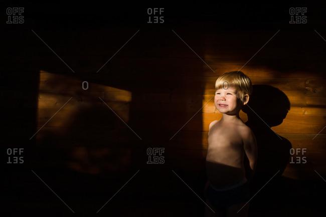 Smiling toddler boy sitting in dark looking toward light