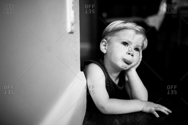 Sad toddler waiting with face resting on hand in black and white
