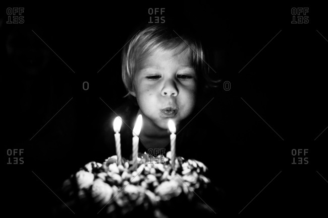 Three year old toddler blowing out candles on birthday cake