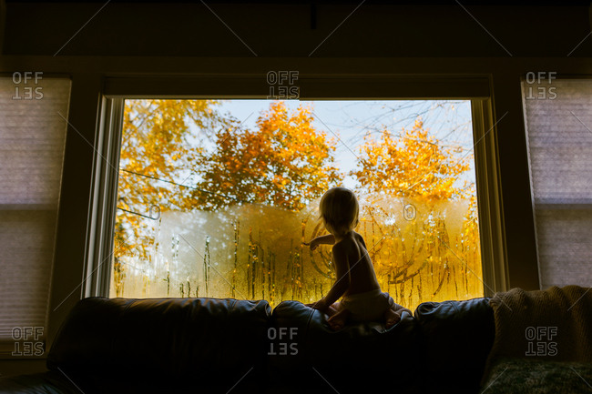 Little kid drawing in window condensation in living room