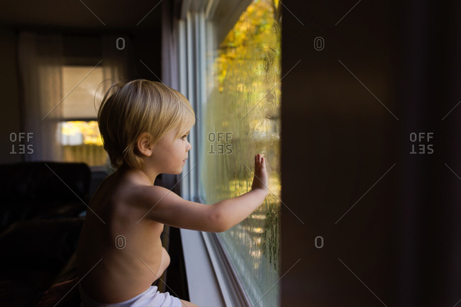 Small toddler looking out window ion dark room