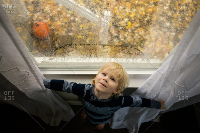 Overhead view of young boy leaning against window sill