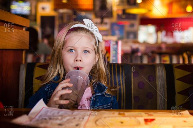 Little girl drinking in coffee shop