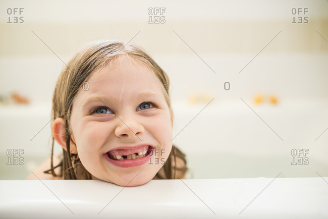 Cute girl with missing teeth taking a bath