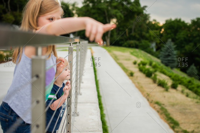 Sister pointing over metal fence with little brother biting wire