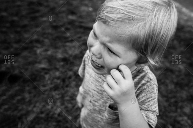 High angle view of small child crying alone outside