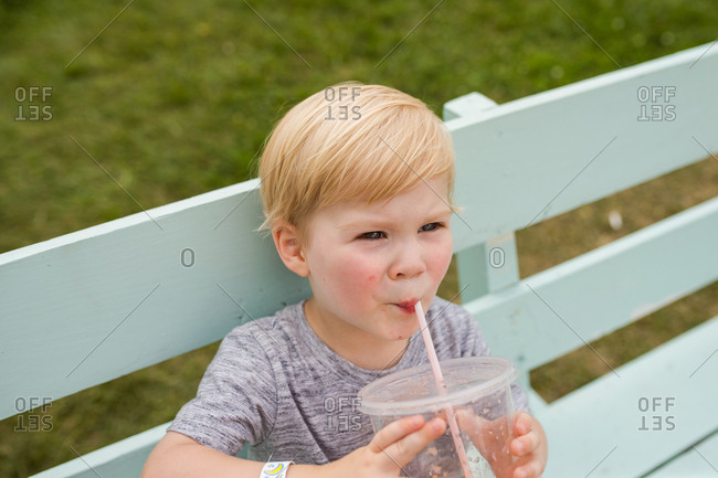Little boy drinking out of a straw alone