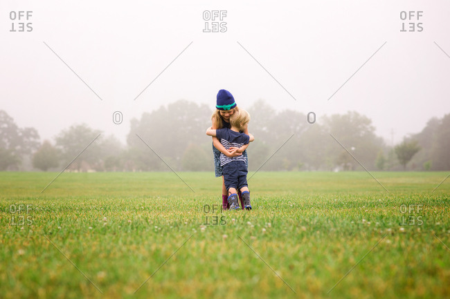 Brother and sister hugging in foggy field