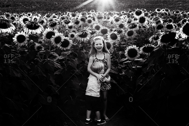 Sweet black and white portrait of siblings hugging in front of field of sunflowers