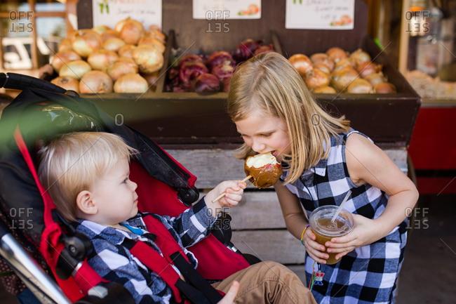 Little brother sharing caramel apple with sister leaning over at market