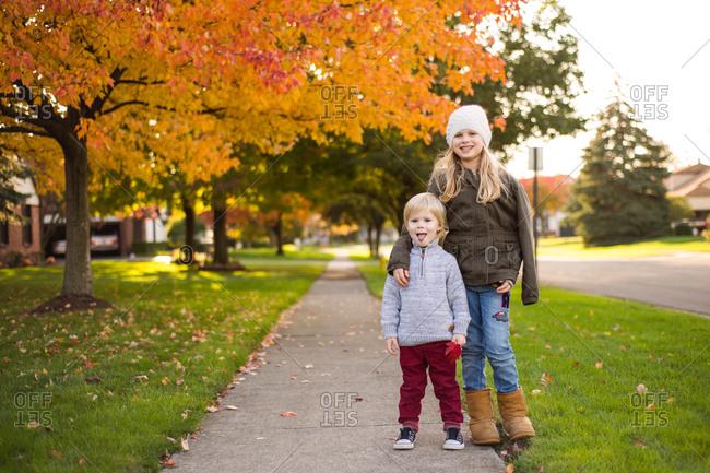 Fall portrait of siblings on sidewalk