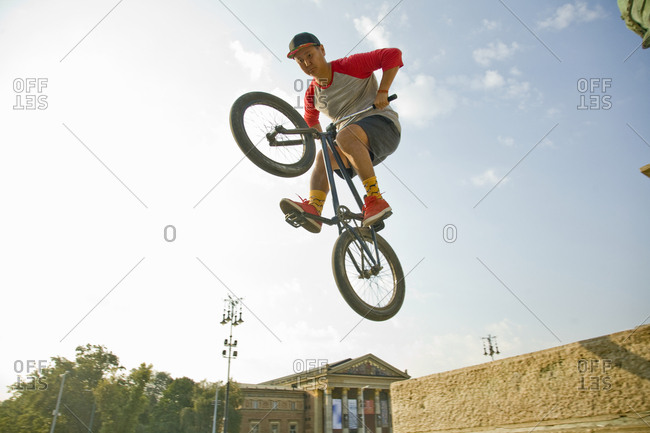 Young Asian man jumping on BMX bike in urban setting in Heroes' Square, Budapest, Hungary