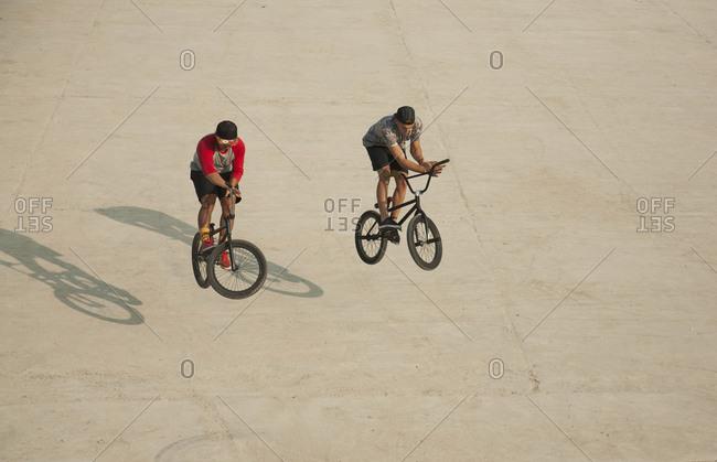 Young men riding BMX bikes on flat land, Budapest, Hungary