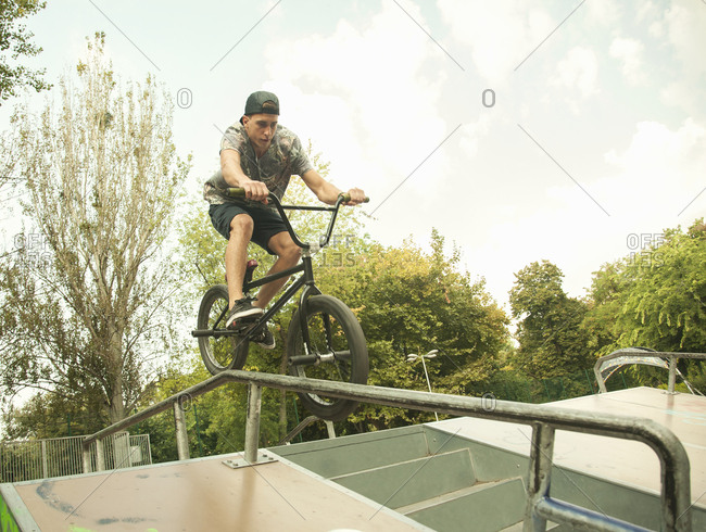 Young man riding BMX bike on jumps at park, Budapest, Hungary