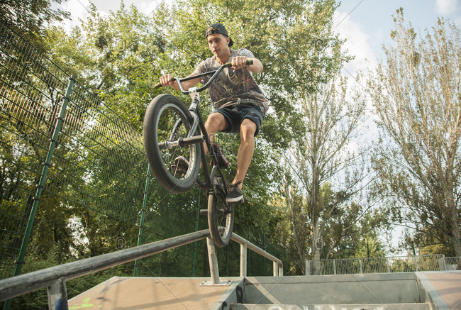 Young man riding BMX bike on jumps in park, Budapest, Hungary