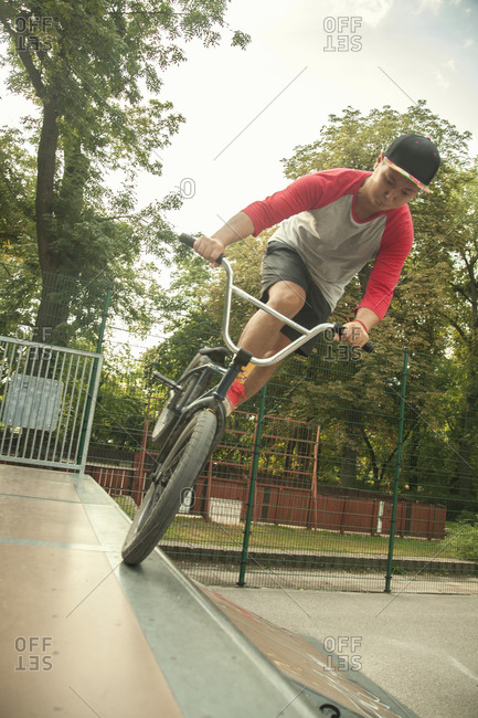 Young Asian man riding BMX bikes on jumps in park, Budapest, Hungary