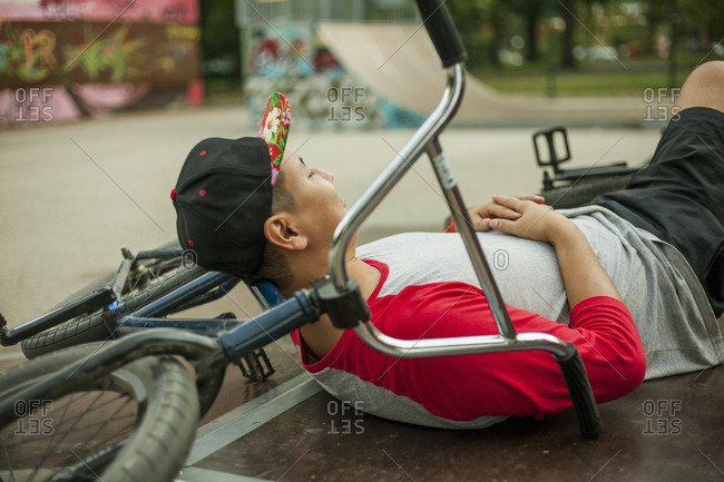 Young Asian man with BMX bike relaxing in BMX park, Budapest, Hungary