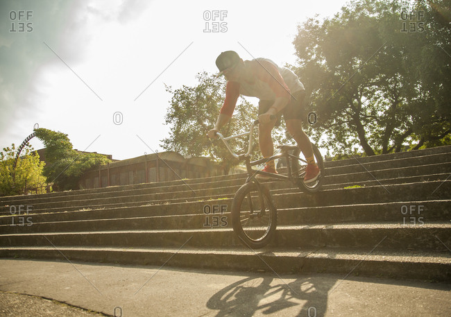 Young Asian man riding BMX bike in park setting, Budapest, Hungary
