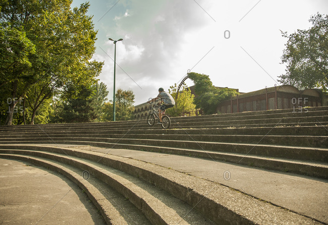 Young man riding BMX bike along steps in park, Budapest, Hungary