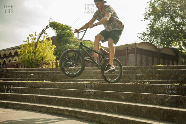 Young man riding BMX bike down steps in park, Budapest, Hungary