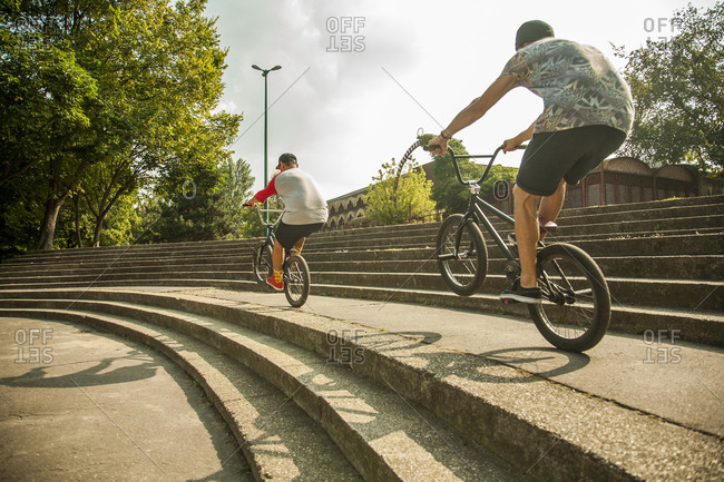 Young men riding BMX bikes along steps in park, Budapest, Hungary
