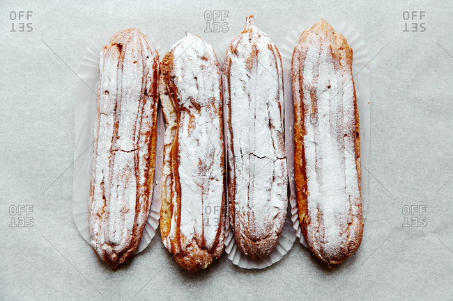 Overhead shot of four eclairs in a row with custard and powdered sugar