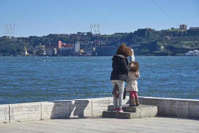 Lisbon, Portugal - 19 February, 2016: Mother helping daughter look across river at scenery with telescope