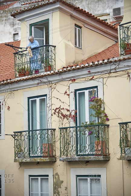 Lisbon, Portugal - 22 January, 2018: Elderly woman looking down from her balcony at the street below