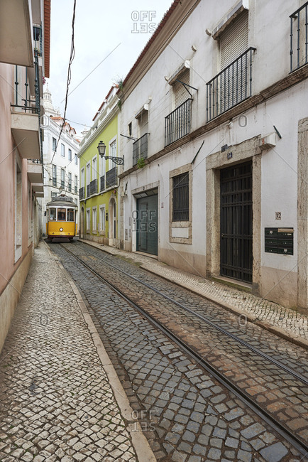 Lisbon, Portugal - 24 February, 2016: Tram squeezing down narrow residential street in old quarter