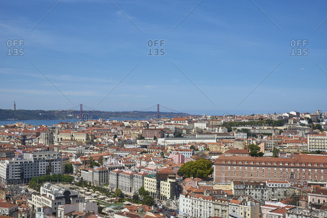 Lisbon, Portugal - 09 June, 2017: Wide angle view of cityscape towards Sanctuary of Christ the King and suspension bridge over the river Tagus