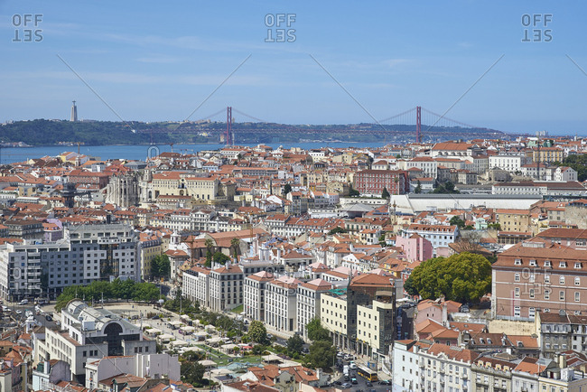 Lisbon, Portugal - 09 June, 2017: Looking over densely packed cityscape towards Ponte 25 de Abril over the river Tagus and Sanctuary of Christ the King