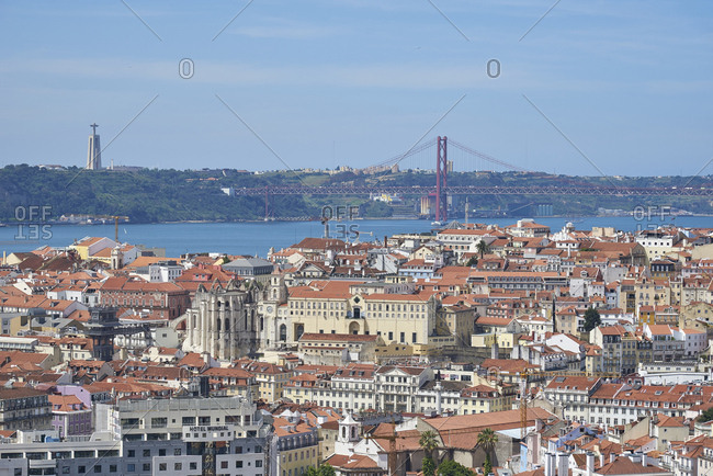 Lisbon, Portugal - 09 June, 2017: Looking over densely packed cityscape towards Sanctuary of Christ the King and suspension bridge over the river Tagus