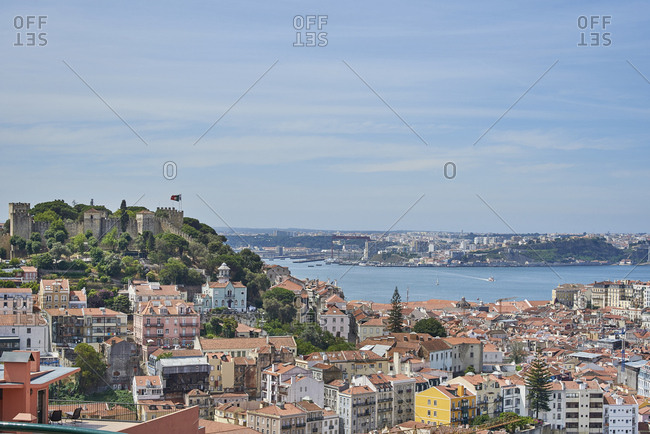 Lisbon, Portugal - 09 June, 2017: Looking over colorful buildings towards Moorish hilltop Sao Jorge Castle and Tagus River