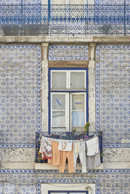 Lisbon, Portugal - 04 December, 2017: Laundry hanging outside window in building facade decorated with Moorish tiles