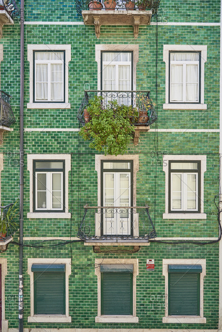 Lisbon, Portugal - 23 December, 2017: Greenery, green tiles and  shutters complete facade of apartment building in old quarter